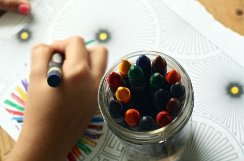 photo of child's hand and jar of crayons