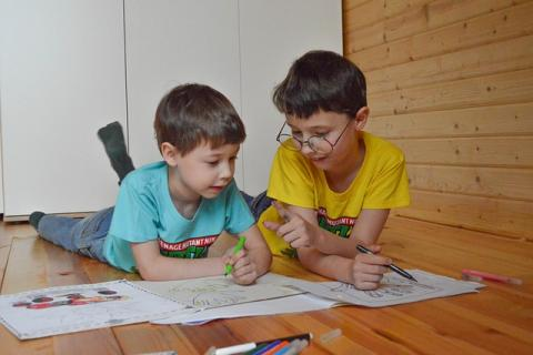 Two boys coloring on floor